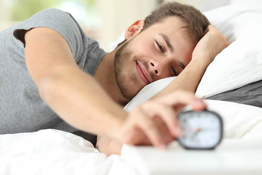 man waking up after a good night's sleep and turning off his alarm