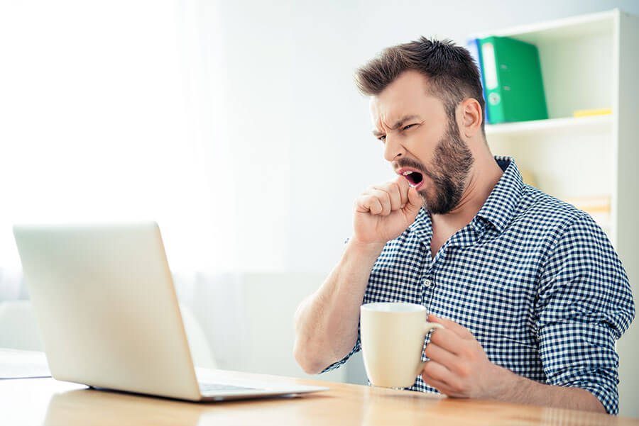 Tired man sitting at a table yawning and drinking coffee