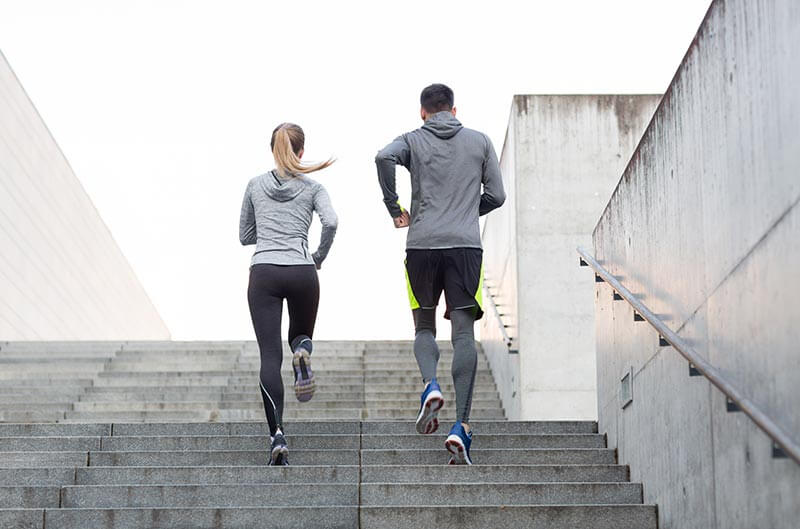 two people jogging on a flight of stairs