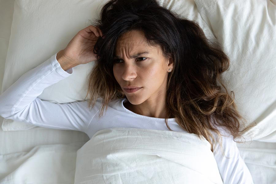 woman in bed who can't sleep due to partner snoring