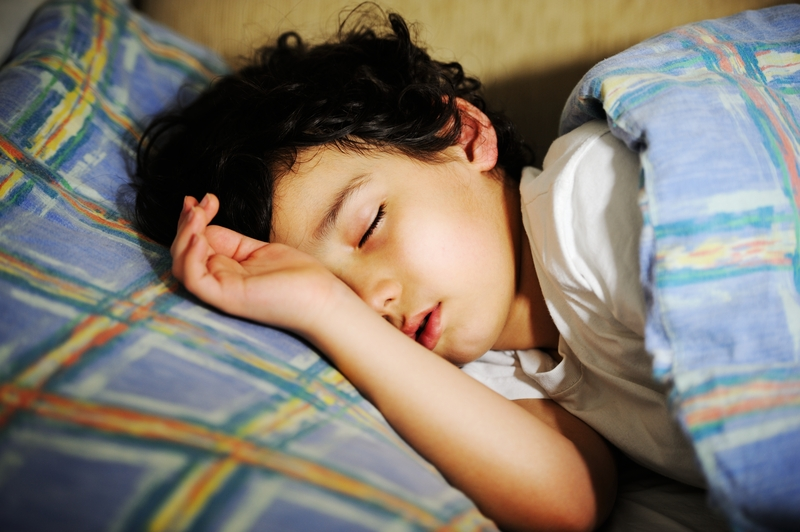 A boy with dark hair sleeping in bed with blue, yellow, and orange bedding
