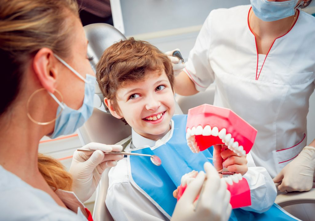 A dentist showing a model of teeth to a happy, smiling boy in the treatment chair