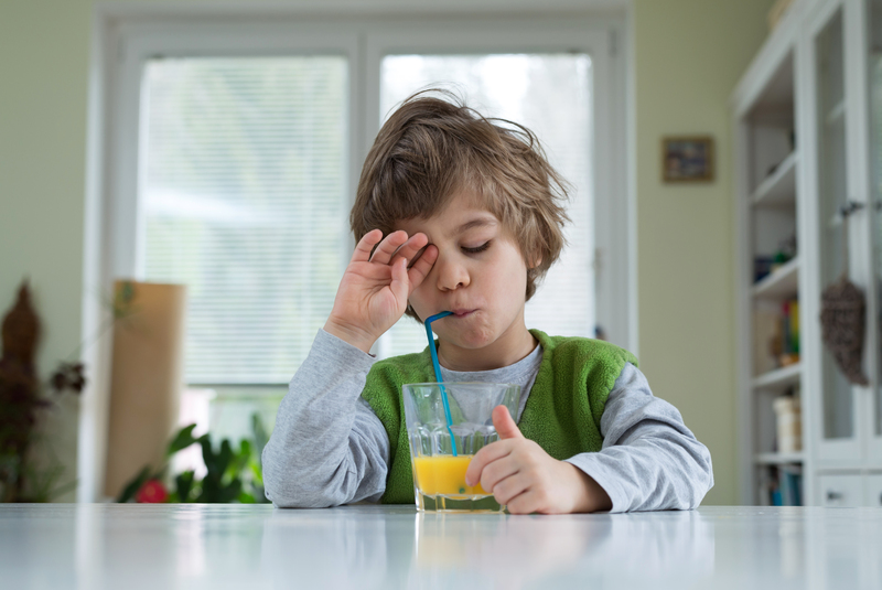 A sleepy looking young boy sitting at the breakfast table drinking orange juice through a straw