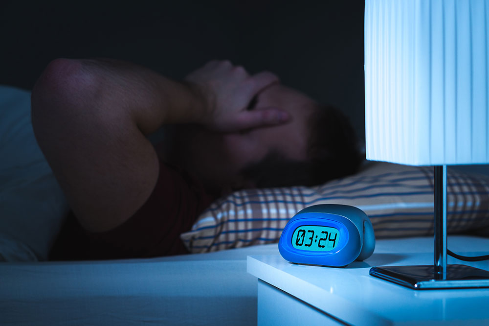 An overweight man lays on his back with his hand over his eyes. It's 3:24 am on a blue clock next to him, but he is struggling to sleep.