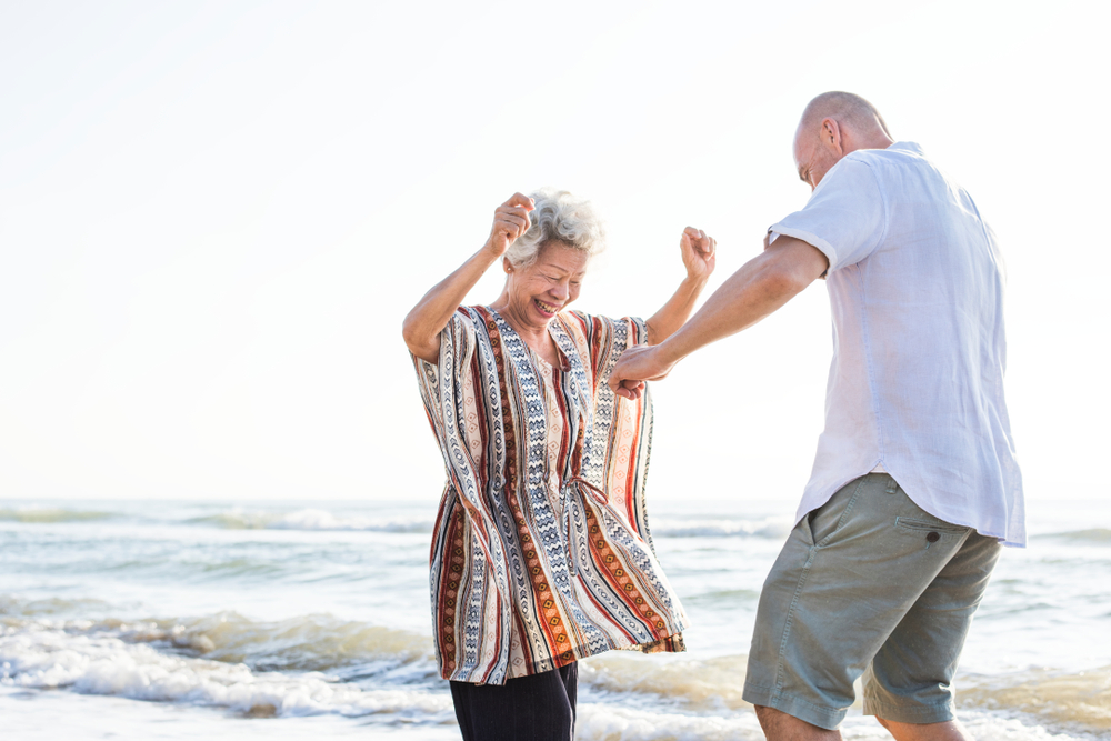 An older Black woman with gray hair wearing a striped tunic is dancing in front of the ocean with a bald man wearing a white shirt and shorts. He's facing toward the woman and away from the camera.