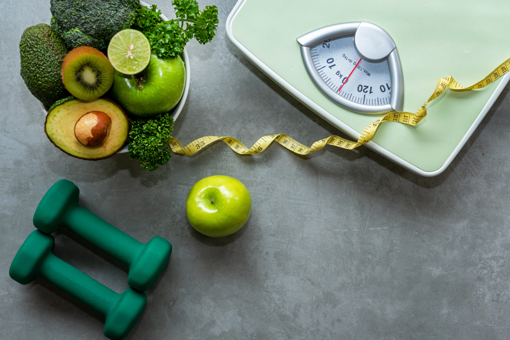 Green fruits and vegetables in a bowl next to dark green weights and a light green scale. An apple sits in the middle, and a yellow measuring tape rests on the scale.